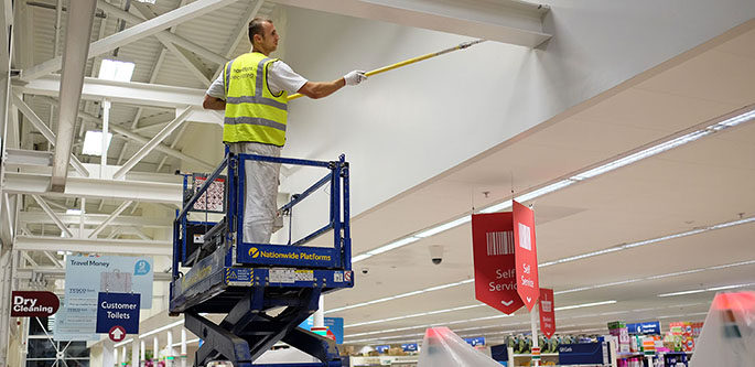 painter rolling walls on cherry picker at tesco extra